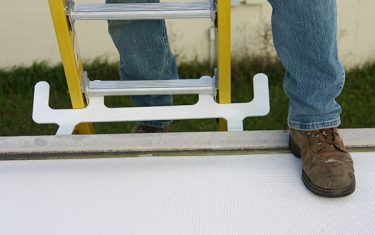Closeup of man shoe. Man stepping from a yellow ladder on to a white roof. Ladder is secured by a Springfield Ladder Anchor.