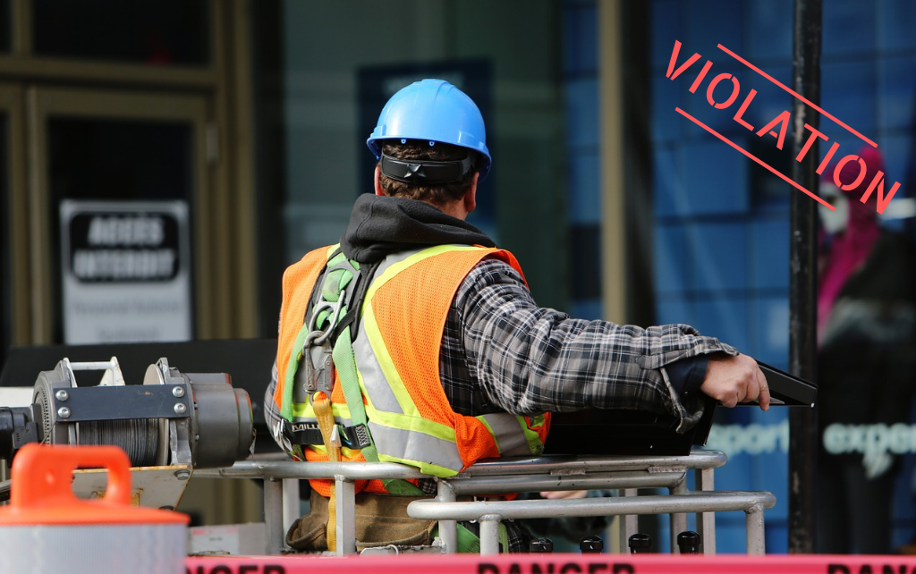 Man in reflective vest, hardhat, and fall protection harness